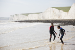 Boy and girl playing in the waves on the beach at Birling Gap, part of the Seven Sisters chalk cliffs range, East Sussex.