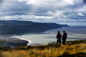 Walkers enjoying the view from Bossington Hill above Porlock Bay, on the Holnicote Estate, Exmoor National Park, Somerset.