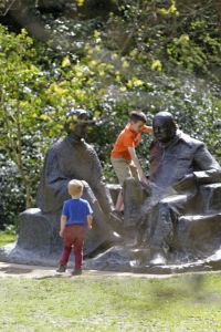 Children playing on a statue of Winston and Clementine Churchill at Chartwell, Kent.