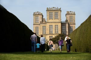 Visitors in the garden with hedges leading to the south front at Hardwick Hall, Derbyshire.
