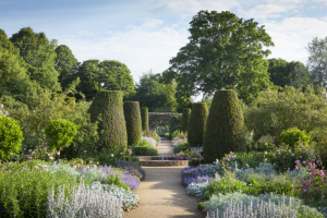 Path through the rose garden in June at Mottisfont, Hampshire, with fountain and yew topiary pillars.