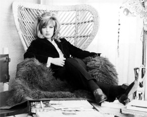 Italian actor Monica Vitti reclines on a Persian lamb rug in a wicker lounge chair while promoting the film, 'Modesty Blaise,' directed by Joseph Losey, England, March 27, 1965. (Photo by Express Newspapers/Courtesy of Getty Images)