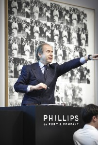 Simon conducting an auction at Phillips de Pury, selling Andy Warhol's Men in Her Life for $63,362,500
